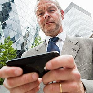 Logo: Businessman using smartphone (Image Source, Image Source, Getty Images)