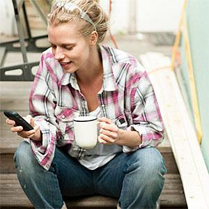 Logo: Woman sitting on steps with smartphone (Image Source, Image Source, Getty Images)
