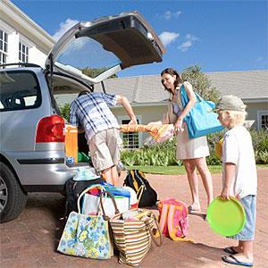 Family of three loading car with luggage, low angle view -- Juice Images, Cultura, Getty Images