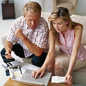 Image: Couple sitting on sofa with bills, using laptop, elevated view Stockbyte/Getty Images