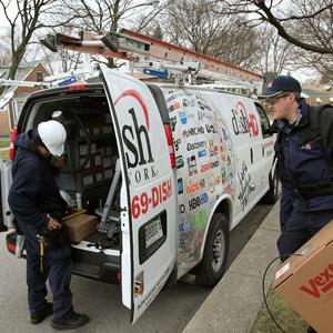 Ivan Olmo (L) and Ryan Winn prepare to install a Dish Network satellite dish at a home on April 6, 2011 in Chicago, Illinois (Scott Olson/Getty Images)