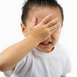 Image: Boy hiding eyes (Ned Frisk Photography/Corbis)