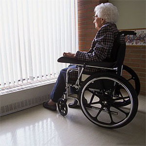 Senior woman on wheelchair looking out of window with blinds -- Design Pics, Don Hammond, Design Pics, Getty Images