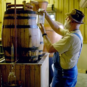Credit: David Goldman/AP&#xA;Caption: Distiller Bob Suchke checks the clarity of a batch of genuine corn whisky before its tempered in the Dawsonville Moonshine Distillery, in Dawsonville, Ga