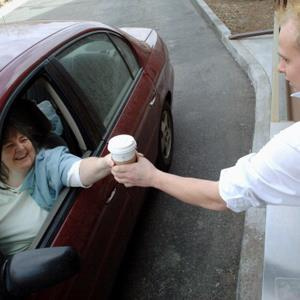 Debra Leewaye gets a Starbucks drink from a drive-through window at Starbucks in Lakewood, Colorado (© Matthew Staver/Bloomberg via Getty Images)