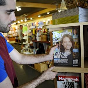 Amadeus Martin, the store supervisor at Book Inc. on Market street, stocks the latest issue of People magazine in San Francisco on Oct. 16, 2009 ( Russel A. Daniels/AP Photo)