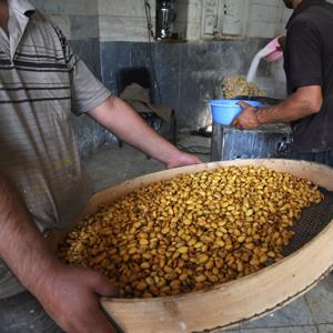 Men go through the pistachio smoking and flavoring process in a small factory in the main bazaar on October 6, 2011 in Tehran, Iran (Kaveh Kazemi/Getty Images)
