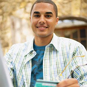 Young man sitting at a table in front of a laptop holding a credit card -- Jack Hollingsworth, Blend Images, Getty Images