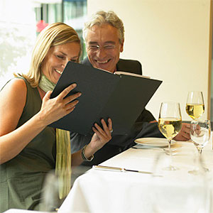 Businessman and woman looking at menu in restaurant, smiling - Jochen Sand, Photodisc, Getty Images
