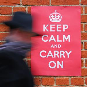 Man walking past a Second World War 'Keep Calm and Carry On' poster (Rawdon Wyatt/Alamy)
