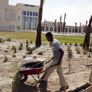 A landscaper works on the grounds of a children's hospital on Aug. 12, 2010 in Basra, Iraq. The hospital is one site among hundreds of projects funded by U.S. taxpayers that remain abandoned or incomplete. (Nabil al-Jurani/AP Photo)
