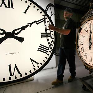 Dan LaMoore moves a clock face at the Electric Time Company plant in Medfield, Mass., on November 3, 2011 ( Elise Amendola/AP)