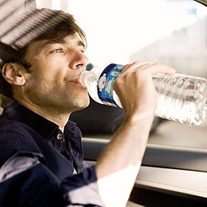 Image: Man drinking bottled water while driving ( PhotoAlto/SuperStock/SuperStock)