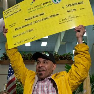 Pedro Quezada, winner of the Powerball lottery, holds up the promotional Powerball jackpot check of $338 million (© Eduardo Munoz/Reuters)