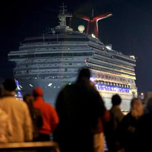 The Carnival Triumph cruise ship is towed towards the dock as spectators watch at the port of Mobile, Alabama on February 14, 2013 (© Lyle Ratliff/Newscom/Reuters)
