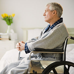 Senior man in wheelchair looking out hospital window (copyright Tetra Images/Getty Images)