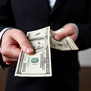 Businessman offering $100 bill (copyright Andrea Bricco/Brand X Pictures/Getty Images)