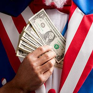Uncle Sam tucking cash into vest (copyright Mike Kemp/Rubberball/Getty Images)