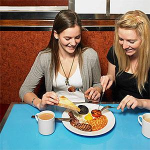 Two women sharing a meal at a diner © Cultura Limited, Superstock