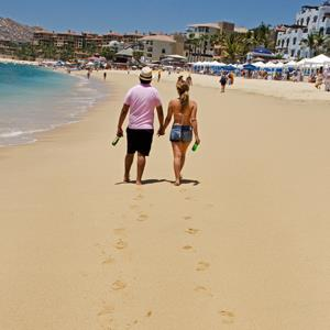 Tourists take a walk on Medano Beach, May 11, 2012, in Cabo San Lucas, Baja California, Mexico (© PAUL J. RICHARDS/AFP/GettyImages)