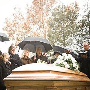 Image: People at a funeral in a cemetery (© Mike Kemp/the Agency Collection/Getty Images)