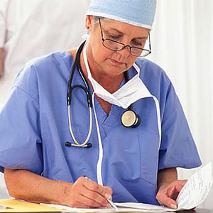 Surgeon with paperwork (copyright Creatas Images/JupiterImages Corporation)