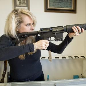 Owner of Ade's Gun Shop, Emily Atkinson, shoulders a Stag Arms 5.56 AR-15 rifle at her shop on Jan. 2, 2013 (© Jebb Harris/The Orange County Register/ZUMA Press/Corbis)
