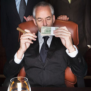 CEO holding money and cigar, copyright Roy McMahon, Corbis