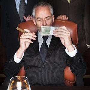 CEO holding money and cigar, copyright Roy McMahon, Corbis
