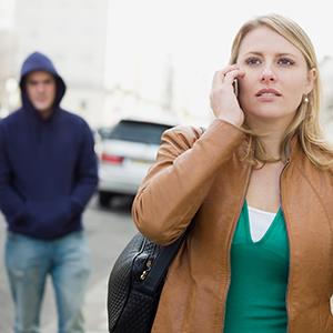 Woman talking on a smartphone while a man walks up behind her (© Image Source/Getty Images)