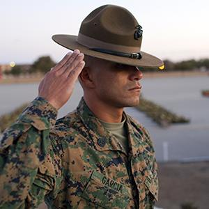 A US Marine Corps Drill Instructor salutes during a dawn ceremony for new Marines on January 8, 2011 at the Marine Corps Recruit Depot on Parris Island, South Carolina (© Robert Nickelsberg/Getty Images)