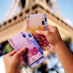 A woman holding Euro bills in front of the Eiffel Tower in Paris, France (copyright Thinkstock/Comstock Images/Getty Images)