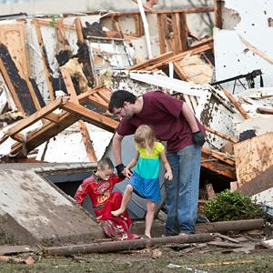 A man & his children walk through debris after a huge tornado struck Moore, Okla., on Monday (© Richard Rowe/Reuters)
