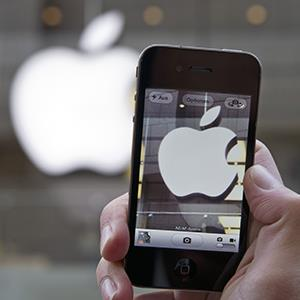 A person takes a photo of an Apple sign with an iPhone (© Lukas Barth/dapd/AP Photo)