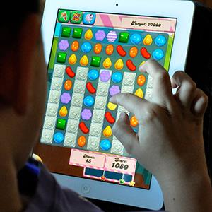 Boy playing 'Candy Crush Saga' on an iPad (Hayley Louize Ballard/Alamy