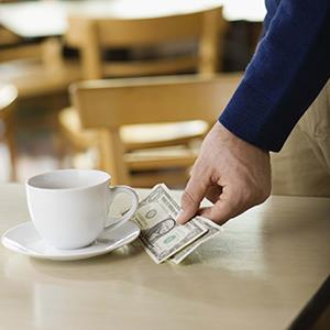 Man leaving tip on table at café (© Jupiterimages/Brand X Pictures/Getty Images)
