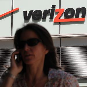 A pedestrian talks on a cellular phone as she walks by a Verizon Wireless store on April 19, 2012 in New York City (© Justin Sullivan/Getty Images)