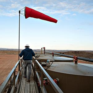 Jerry Myers, district manager for Kodiak Oil & Gas Corp., walks along a catwalk at the top of crude oil storage tanks in Watford City, North Dakota on Feb. 14, 2012 (© Daniel Acker/Bloomberg via Getty Images)