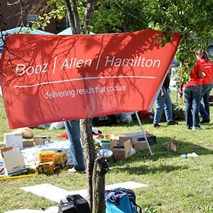 Photo of a Booz Allen Hamilton sign hanging at a volunteer event (© Booz Allen Hamilton via Facebook)