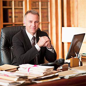 Smiling lawyer sitting at desk in office © Chris Ryan, OJO Images, Getty Images