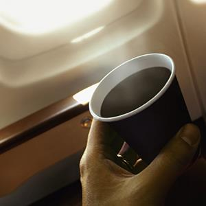 Person holding a coffee cup on an airplane (© VEER Steven Puetzer/Solus/Getty Images)