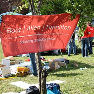 Photo of a Booz Allen Hamilton sign hanging at a volunteer event (© Booz Allen Hamilton via Facebook)