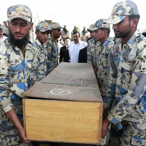 Pakistani soldiers carry coffins of foreign tourists at Chaklala airbase in Rawalpindi, Pakistan on June 23, 2013 (© STR/AFP/Getty Images)