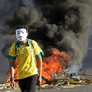 A masked protester walks away from a burning barricade near the Castelao stadium in Fortaleza, Brazil, on June 19, 2013 (© Andre Penner/AP)