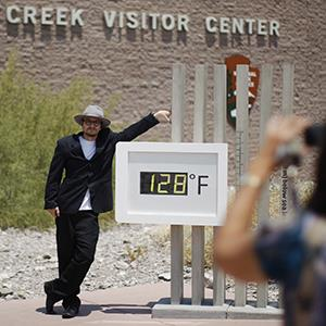 Kevin Martin poses for a snapshot by an unofficial thermometer reading at Furnace Creek Visitor Center as a heat wave spreads across west on June 30, 2013 in Death Valley National Park, Calif. (© David McNew/Getty Images)