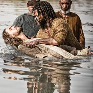 This publicity image released by History shows Diogo Morcaldo as Jesus, center, being baptized by Daniel Percival, as John, in a scene from