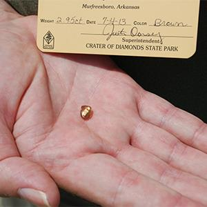 The champagne brown Patriot Diamond sparkles in the hand of finder Terry Staggs (Courtesy of Arkansas State Parks)