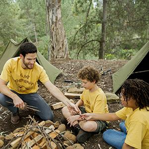 Campers building a fire with their camp counselor (© Hero Images/Lifesize/Getty Images)