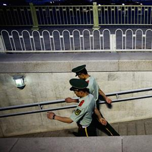 File photo of two Chinese policemen on patrol on June 3, 2013 in Beijing, China (© Feng Li/Getty Images)