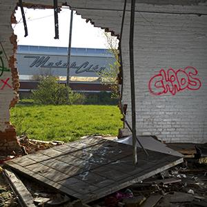 The Motor City Casino and hotel is seen through a hole in the wall of an abandoned building along Grand River Avenue on May 1, 2013 in Detroit, Michigan (© Ann Hermes/The Christian Science Monitor via Getty Images)